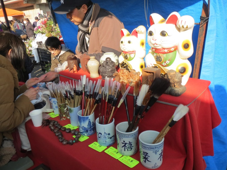 Maneki neko (waving cats) and calligraphy brushes on sale.