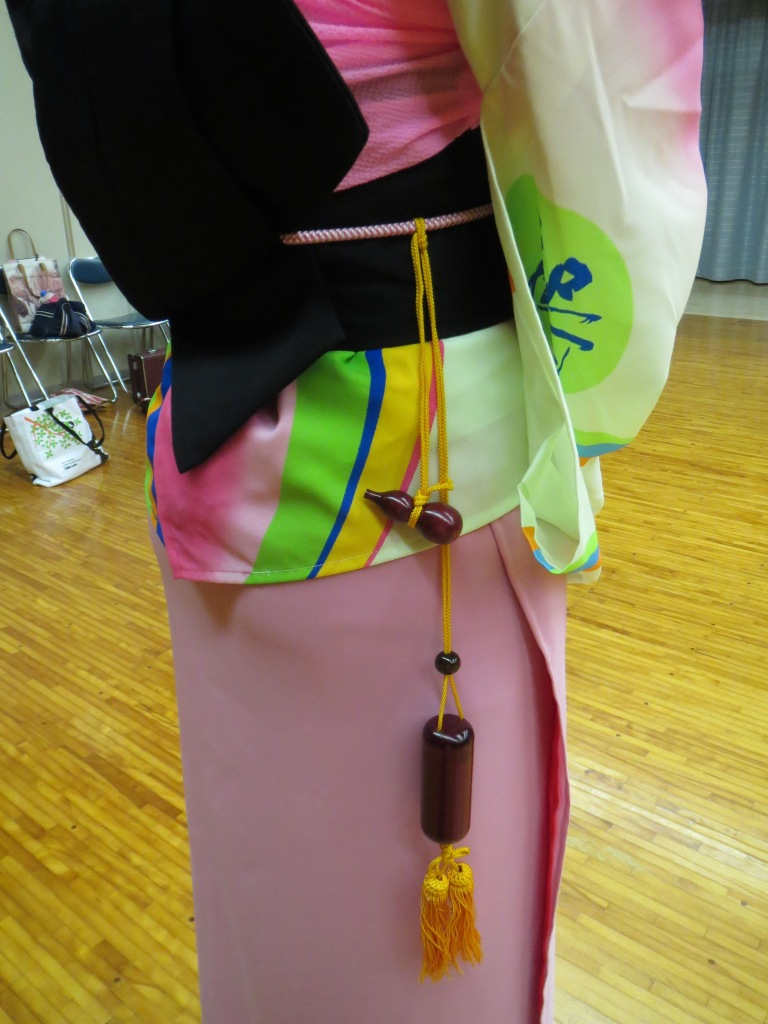 The inrou hangs unobtrusively on the right side near the musubi. In this picture, you can also see just how short the kimono is. The pink you see is the susoyoke plainly visible.