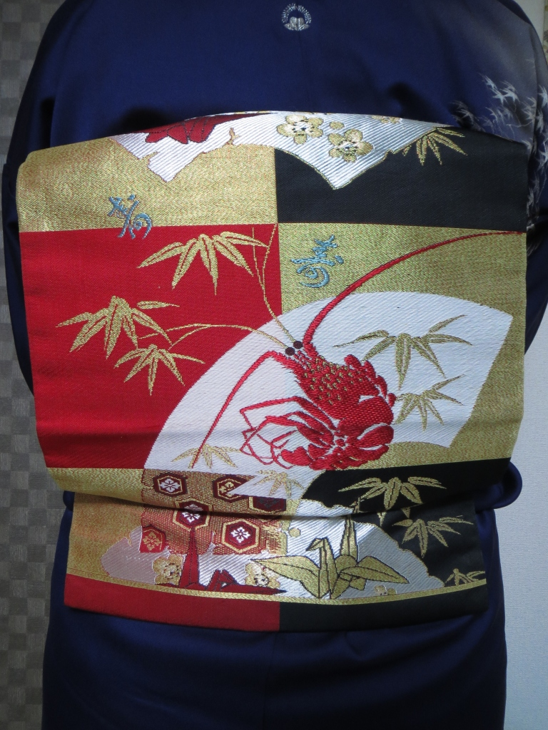 "This obi has so much going on!  I can only wear it at New Years.  the lobster is an auspicious motif that has ties to the special food served on New Years (osechi).  The bamboo and cranes are also auspicious.  The kanji is ""kotobuki"" and it means celebration or a long life."